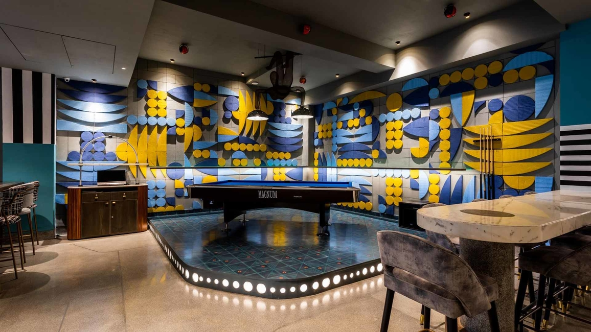 The games/pool area with the eye-catching wall mural and ceiling
