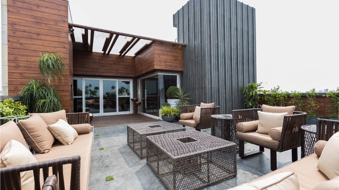 With the bungalow rising imposingly in the background, this terrace space dotted with potted plants and luxurious seating options has welcome warmth to it.