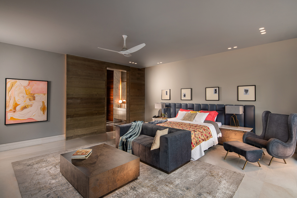A neutral palette comes alive with plush furniture pieces and bed with a beautifully stitched headboard. The sculptural chair, footstool and artworks add interest.